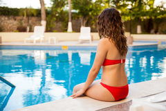 Pretty brunette sitting by the pool Stock Photos