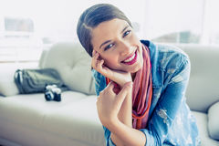 Pretty brunette sitting on sofa looking at camera Royalty Free Stock Photo
