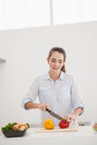 Pretty brunette slicing up peppers Stock Photography