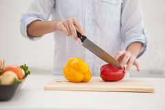 Pretty brunette slicing up peppers Stock Photos