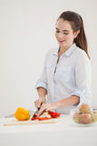 Pretty brunette slicing up peppers Royalty Free Stock Image