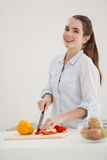 Pretty brunette slicing up peppers Stock Photo