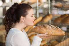 Pretty brunette smelling loaf of bread Royalty Free Stock Photos
