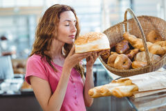 Pretty brunette smelling loaf of bread Royalty Free Stock Image