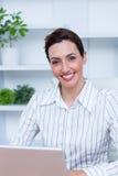 Pretty brunette smiling businesswoman using laptop Stock Photos