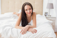 Pretty brunette smiling at camera in bed Royalty Free Stock Photos
