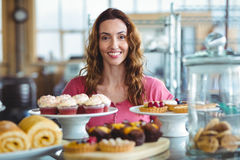 Pretty brunette smiling at camera behind counter Stock Photos
