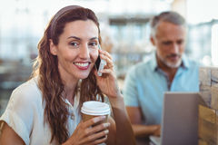 Pretty brunette smiling at camera and having phone call Stock Photo