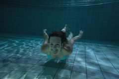 Pretty brunette smiling at camera underwater Stock Photos
