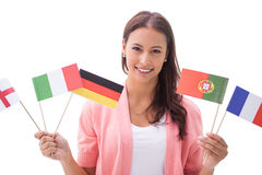 Pretty brunette smiling and holding flags Royalty Free Stock Images