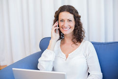 Pretty brunette speaking on the phone while using her laptop Royalty Free Stock Photos