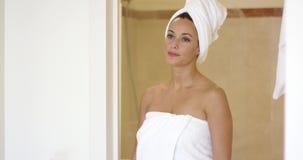 Pretty brunette stands in bathroom door frame stock video