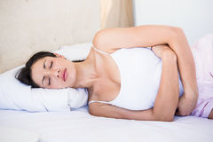 Pretty brunette with stomach pain on bed. Pretty brunette with stomach pain lying on bed Royalty Free Stock Photos