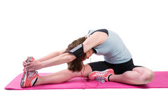 Pretty brunette stretching her leg on exercise mat Stock Image
