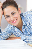 Pretty brunette student smiling at camera while lying on the floor in front of assignments Royalty Free Stock Images