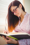 Pretty brunette studying beside window Royalty Free Stock Photos