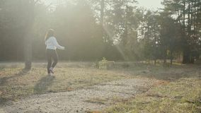Pretty brunette walks with a Golden-colored Labrador in the spring forest stock footage