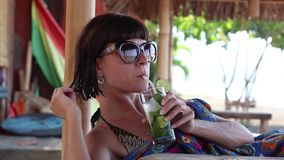 Pretty brunette in sunglasses lies in gazebo with a cocktail on a sunny day. Tropical Bali island, Amed, Indonesia. Pretty brunette in sunglasses lies in gazebo stock video footage
