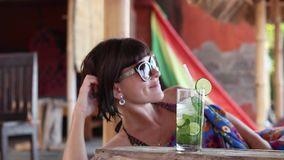 Pretty brunette in sunglasses lies in gazebo with a cocktail on a sunny day. Tropical Bali island, Amed, Indonesia. Pretty brunette in sunglasses lies in gazebo stock footage