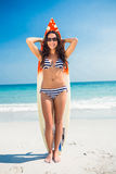 Pretty brunette with a surfboard looking at camera Royalty Free Stock Photos