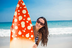 Pretty brunette with a surfboard looking at camera Stock Images