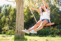 Pretty brunette swinging in park Royalty Free Stock Image