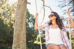 Pretty brunette swinging in park Stock Photos