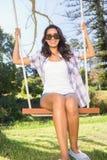 Pretty brunette swinging in park Stock Images