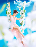 Pretty brunette swinging among white clouds Royalty Free Stock Image