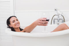 Pretty brunette taking a bath with glass of wine Royalty Free Stock Photo