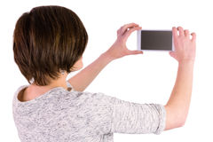 Pretty brunette taking a picture with her smartphone Royalty Free Stock Images