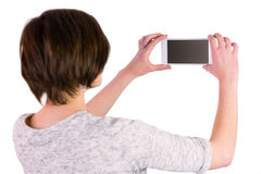 Pretty brunette taking a picture with her smartphone Stock Images