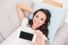 Pretty brunette taking a selfie on couch Royalty Free Stock Photo