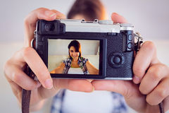 Pretty brunette taking a selfie with retro camera on couch Stock Photo