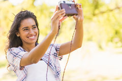 Pretty brunette taking a selfie with retro camera in the park Stock Images