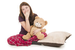 Pretty brunette teenage girl in pajamas pyjamas. Waking up huggin teddy bear isolated on white Royalty Free Stock Images