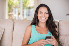 Pretty brunette texting with her smartphone. At home in the living room Royalty Free Stock Photography