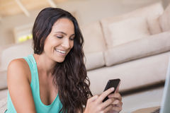 Pretty brunette texting with her smartphone. At home in the living room Stock Photos