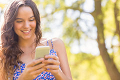 Pretty brunette texting in the park Royalty Free Stock Images