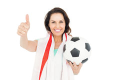 Pretty brunette with thumbs up holding soccer ball Stock Images