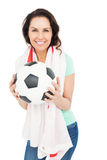 Pretty brunette with thumbs up holding soccer ball Royalty Free Stock Photography