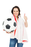 Pretty brunette with thumbs up holding soccer ball. Over white background Royalty Free Stock Photo