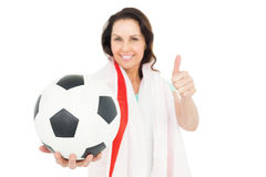 Pretty brunette with thumbs up holding soccer ball. Over white background Royalty Free Stock Photos