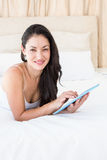 Pretty brunette touching tablet computer on couch Stock Images