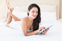 Pretty brunette touching tablet computer on couch Stock Image