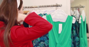Pretty brunette trying jacket in store stock footage