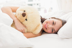 Pretty brunette under the duvet with teddy bear Royalty Free Stock Photo