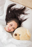 Pretty brunette under the duvet with teddy bear Royalty Free Stock Images