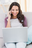 Pretty brunette using her laptop. At home in the living room Royalty Free Stock Images