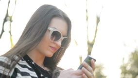 Pretty brunette using her mobile phone with touch screen standing in the park during sunny spring day. portrait of. Amazing Young Woman with Smartphone and stock video footage